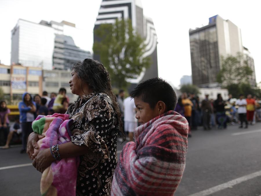 Personas esperan en la calle mientras escuchan la alarma sísmica en la Ciudad de México
