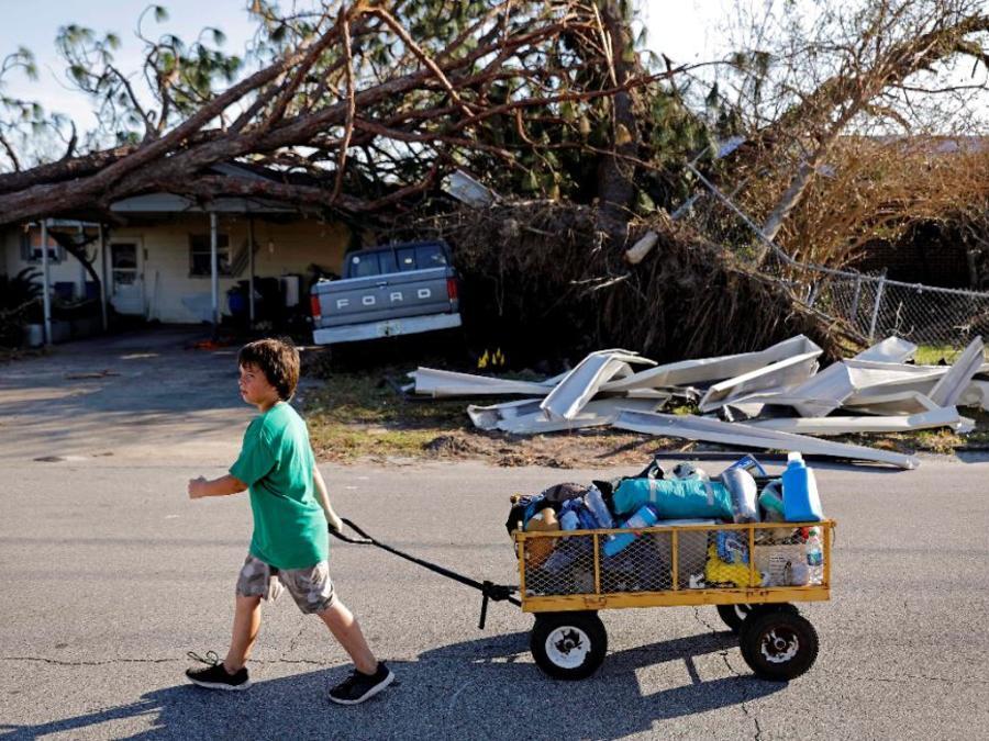 Un niño de 11 años saca eb un carrito las pertenencias de su familia de su hogar destrozado en Springfield, Florida.