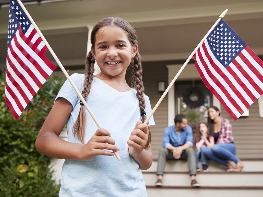 Niña sosteniendo banderas de Estados Unidos