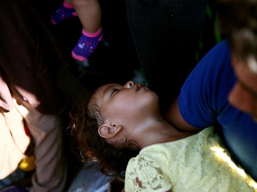 Una niña migrante cae ante el insoportable calor en el puente que conecta a Guatemala con México.