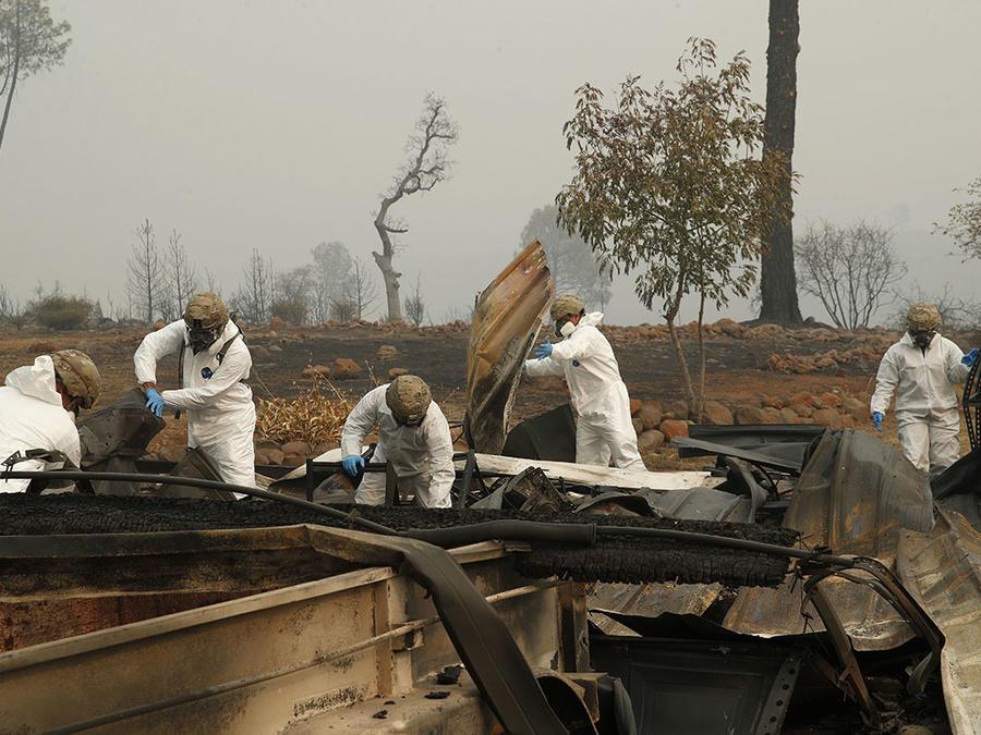 Miembros del Army National Guard de California buscan restos humanos en una casa que fue arrasada por las llamas,