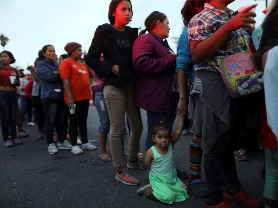 Migrantes centroamericanos, inetgrantes de la caravana centroamericana que intenta llegar a Estados Unidos, esperan este lunes una cena donada en Mexicali, México.
