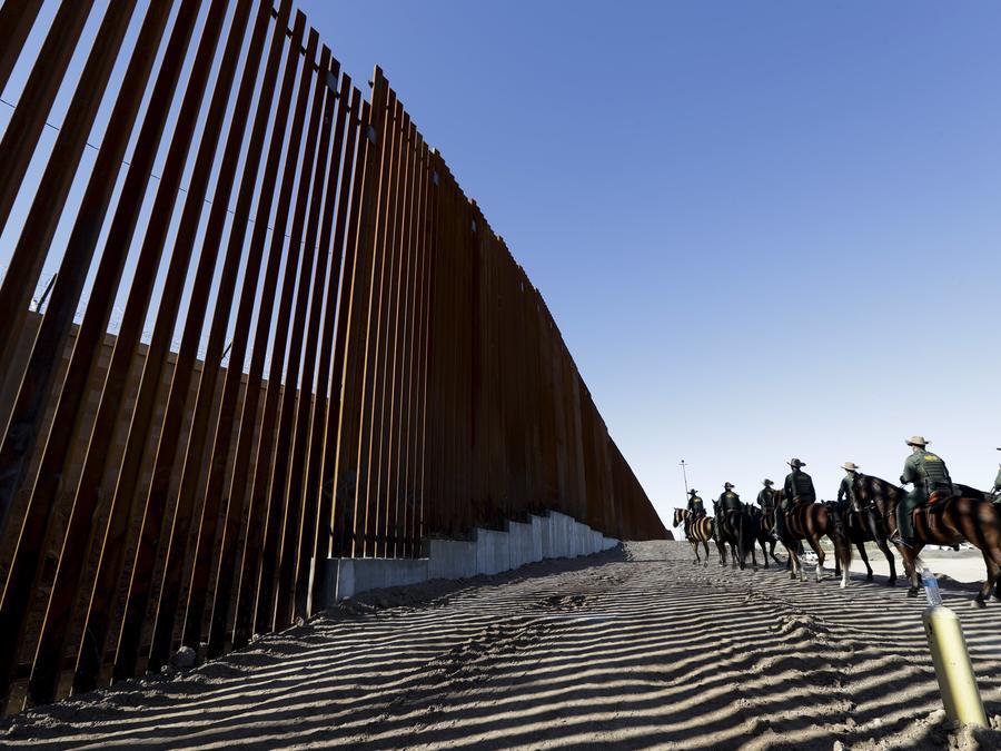 Agentes de la Patrulla Fronteriza montados viajan a lo largo de una estructura de muro fronterizo reforzada