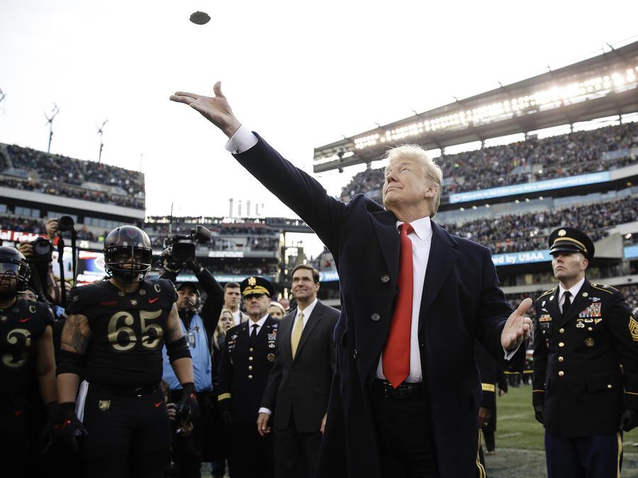 Donald TrumpTrump lanza una moneda al aire al inicio de un partido de la NCAA el domingo.
