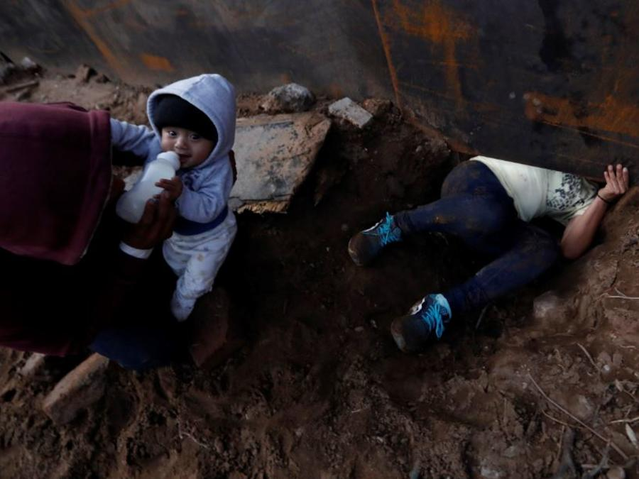 El migrante hondureño Joel Méndez, de 22 años, alimenta a su hijo de 8 meses Daniel mientras su compañera, Yesenia Martínez, cruza la frontera con EE.UU.