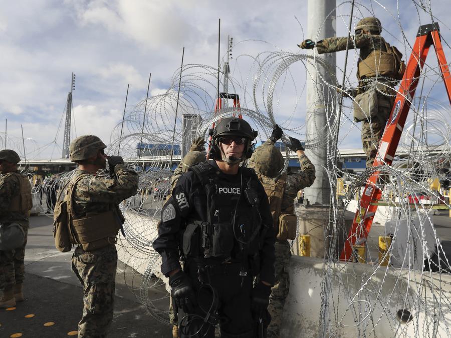 Soldados instalan el alambre de púas a lo largo de la frontera con México mientras un agente de la Patrulla Fronteriza hace guardia cerca del cruce de San Isidro