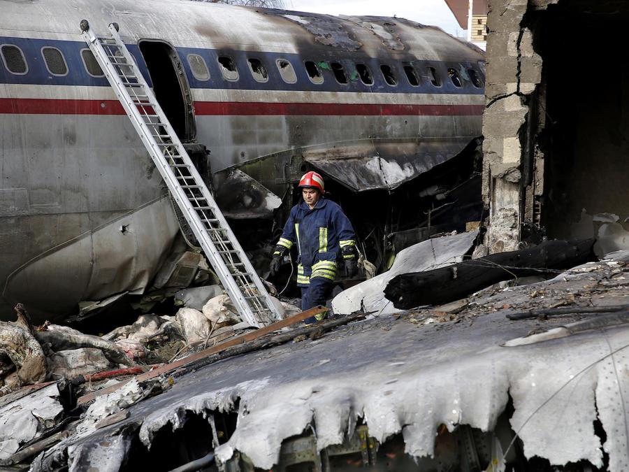 Un trabajador de los equipos de rescate entre los restos del aparato siniestrado este lunes en Irán.