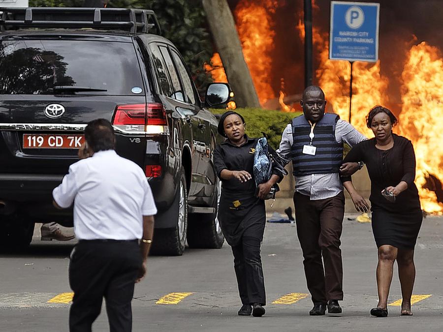 Fuerzas de seguridad ayudan a civiles a abandonar la escena mientras  una bola de fuego engulle a los automóviles que estaban detrás de ellos en un complejo turístico este martes en Nairobi
