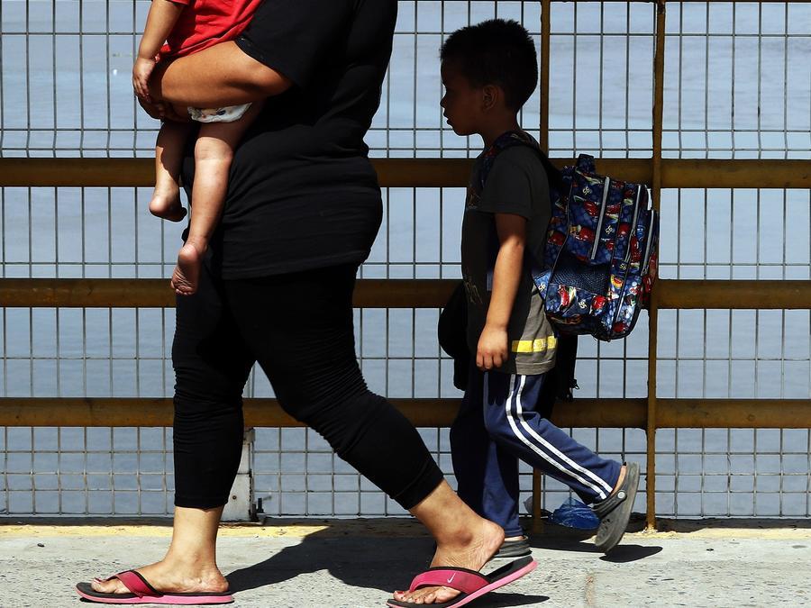 Una madre y sus dos hijos cruzan el puente del río Suchiate mientras los migrantes centroamericanos cruzan la frontera entre Guatemala y México, cerca de Ciudad Hidalgo, estado de Chiapas, México, el 17 de enero de 2019/AP