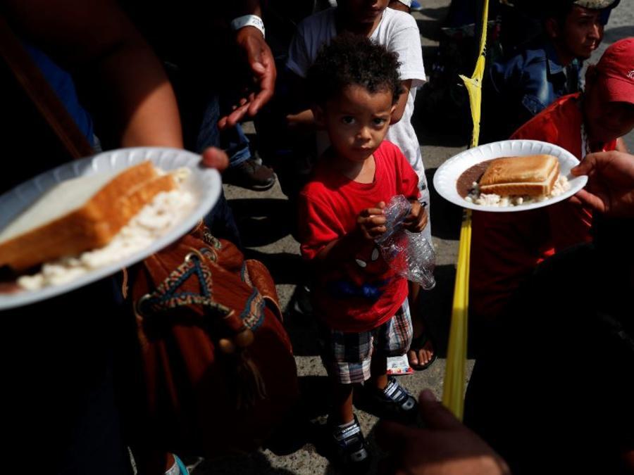 Migrantes centroamericanos almuerzan este domingo, cortesía de las autoridades mexicanas, mientras esperan que se procesen sus visas humanitarias en un puente fronterizo entre México y Guatemala.