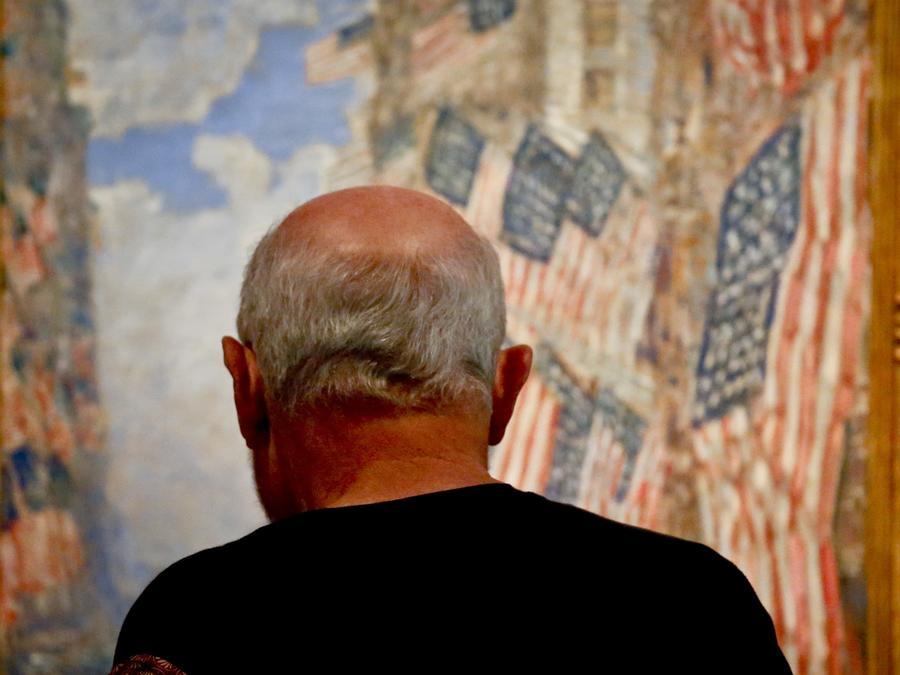 Un ciudadano estadounidense es fotografiado cerca de un cuadro con varias banderas del país en una de las sedes de USCIS en Nueva York.