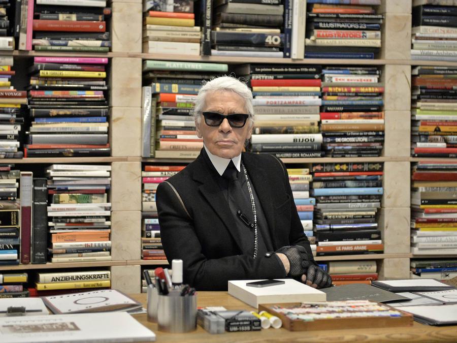 Fotografía de archivo del 14 de febrero de 2014 del diseñador de modas Karl Lagerfeld frente a sus libros antes de la inauguración de una exhibición en el museo Folkwang en Essen, Alemania.