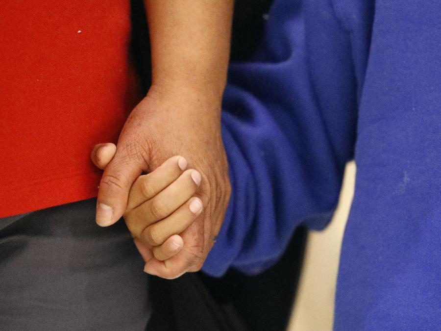 Fotografía de archivo de un niño migrante separado de su familia sosteniendo la mano de su madre después de la reunificación