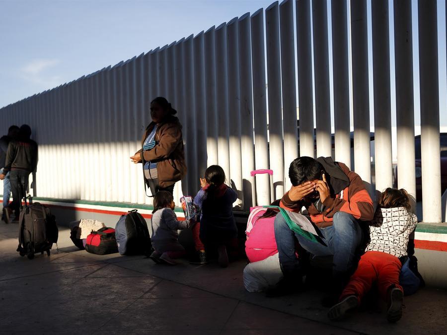 Un migrante con sus hijos espera solicitar asilo a los Estados Unidos en la frontera con México en Tijuana el 25 de enero de 2019.