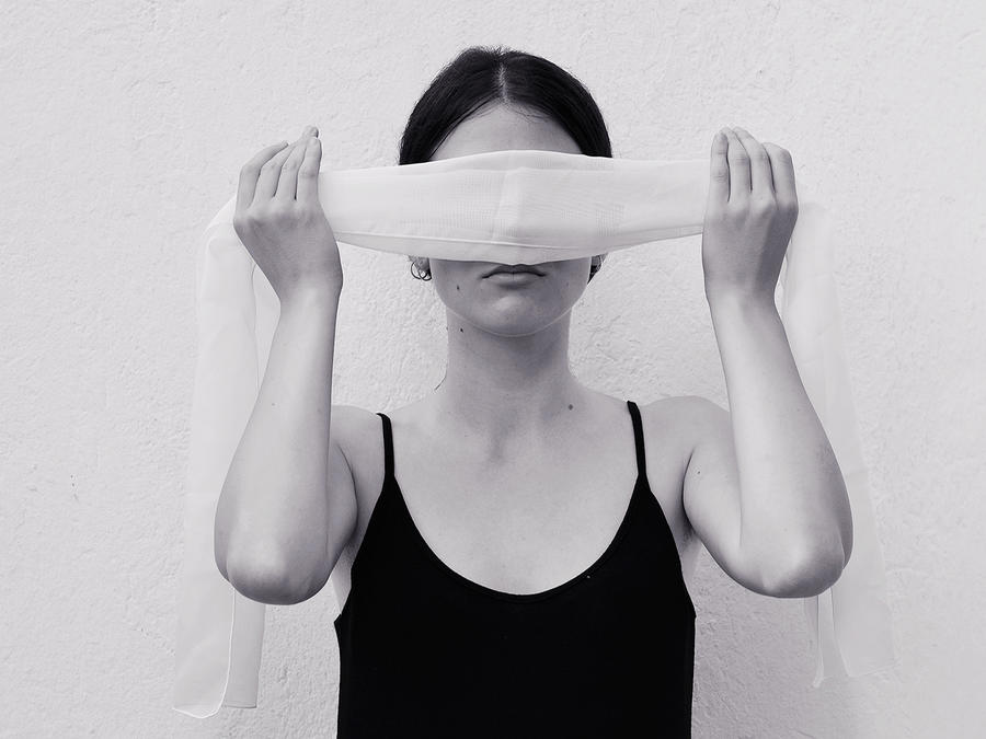 Young Woman Blindfolding While Standing By Wall