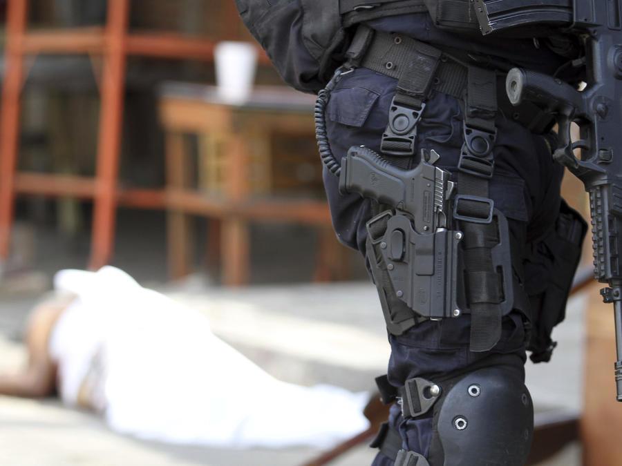 Un agente junto al cadáver de un hombre asesinado en enero en México.