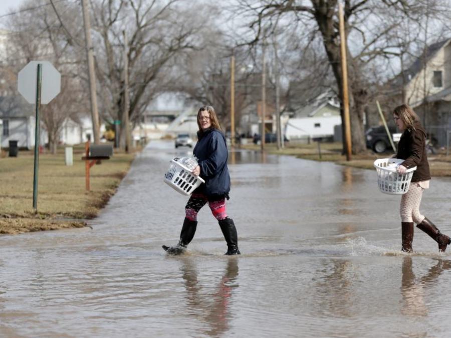 Akashi Haynes, a la izquierda, y su hija Tabitha Viers este lunes rescatan sus pertenencias de su casa inundada en Fremont, Nebraska.