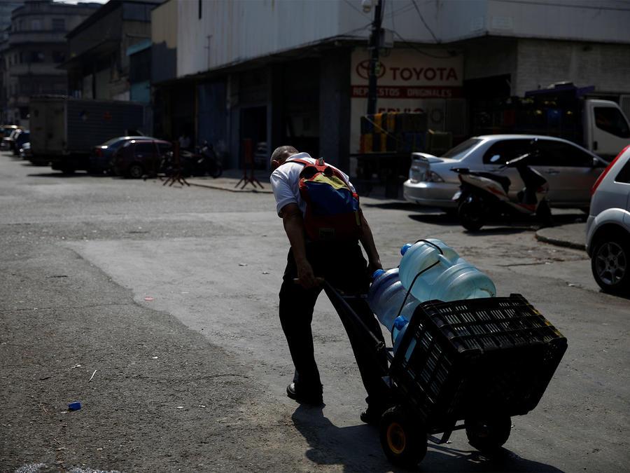 Un hombre arrastra agua en Venezuela