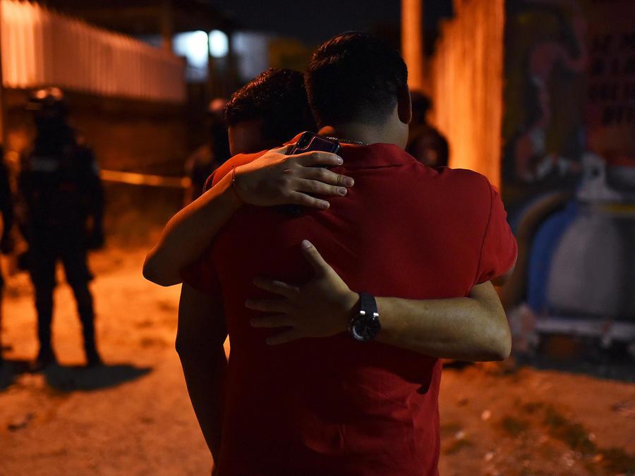 Dos personas se abrazan tras masacre en un club nocturno de Veracruz