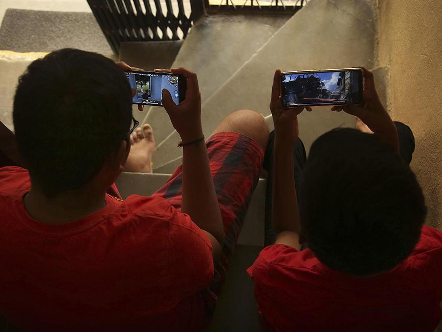 Dos niños juegan en sus celulares.