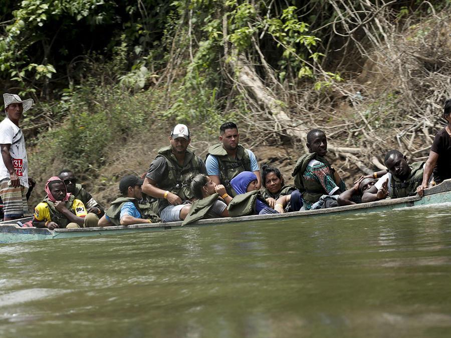 Varios migrantes atraviesan el peligroso río Turquesa en su camino hacia Peñitas, en Panamá, después de caminar durante días en la selva conocida como el Darién.