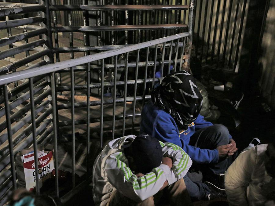 Inmigrantes centroamericanos cubren su cara mientras esperan en el puerto de entrada de Otay Mesa, en San Diego.