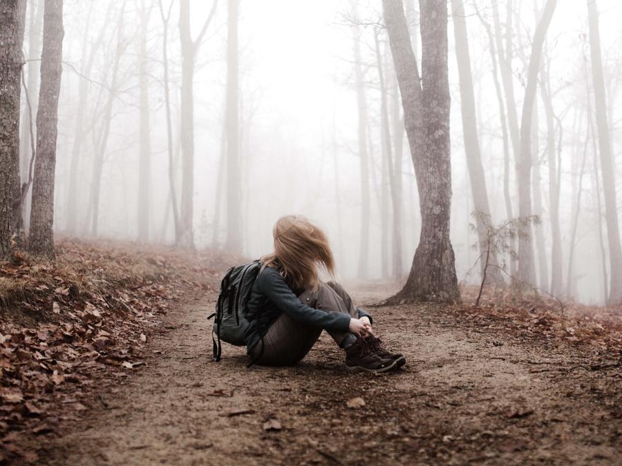 Joven triste en medio del bosque