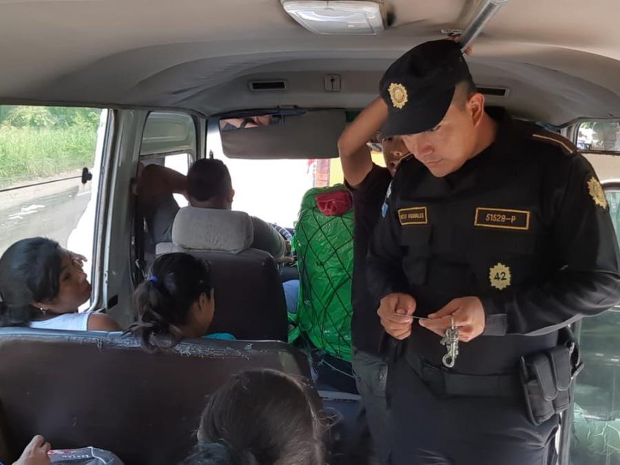 Un agente de la Policía Nacional Civil de Guatemala revisa la documentación de los pasajeros de un autobús.