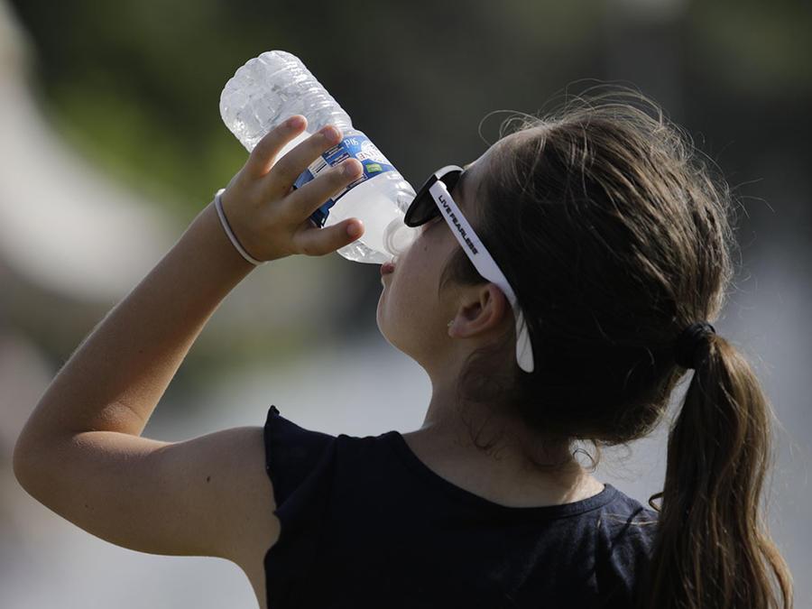 Una joven toma agua para aliviar el calor.