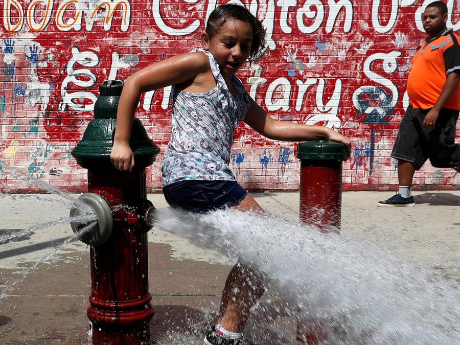 Una niña se refresca en las calles de EEUU en medio de la ola de calor
