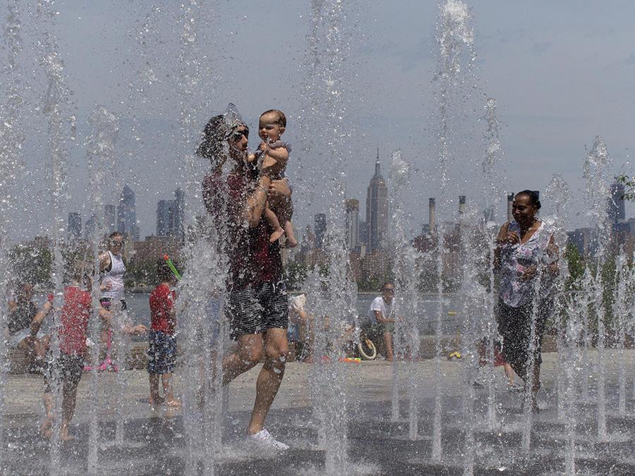 Varias personas se alivian del calor rn una fuente cercana al edificio Empire State en Williamsburg, Brooklyn.