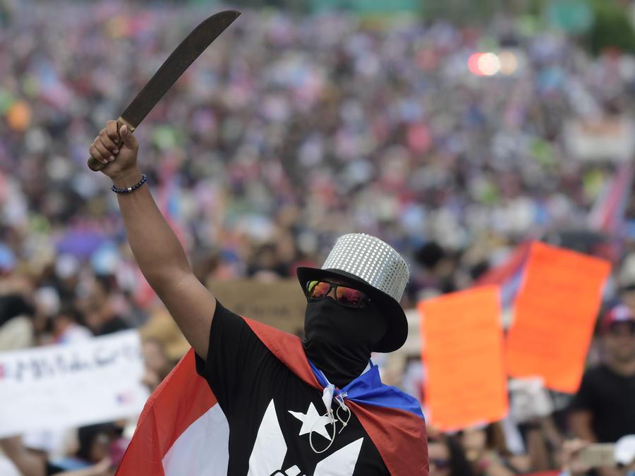 Un manifestante blande un machete durante una marcha para exigir la renuncia del gobernador Ricardo Rosselló, en San Juan, Puerto Rico, el lunes 22 de julio de 2019.