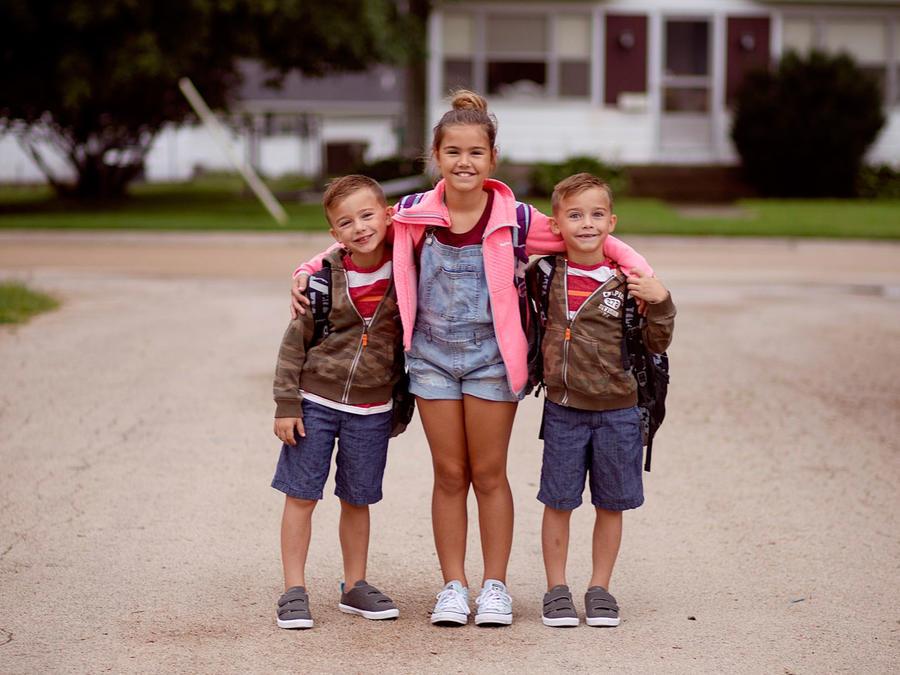 Niños hermanos sonriendo y abrazados fuera de casa