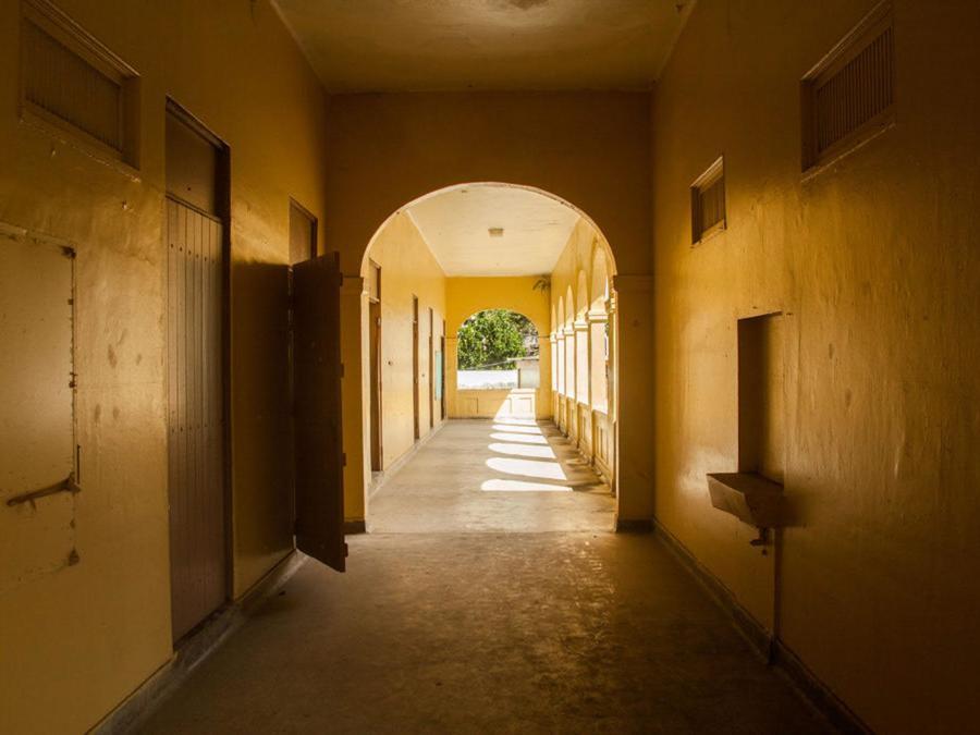 El sol brilla en un pasillo vacío en el segundo nivel de la antigua escuela Pedro G. Goyco en San Juan.