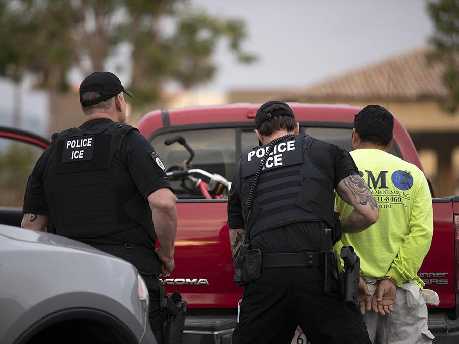 Agentes de ICE detienen a un inmigrante indocumentado.