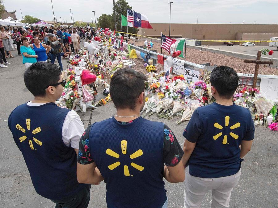 Empleados de Walmart contemplan un memorial improvisado a las víctimas de la tienda en El Paso