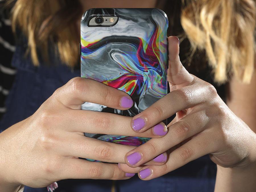 Una joven sostiene su celular.