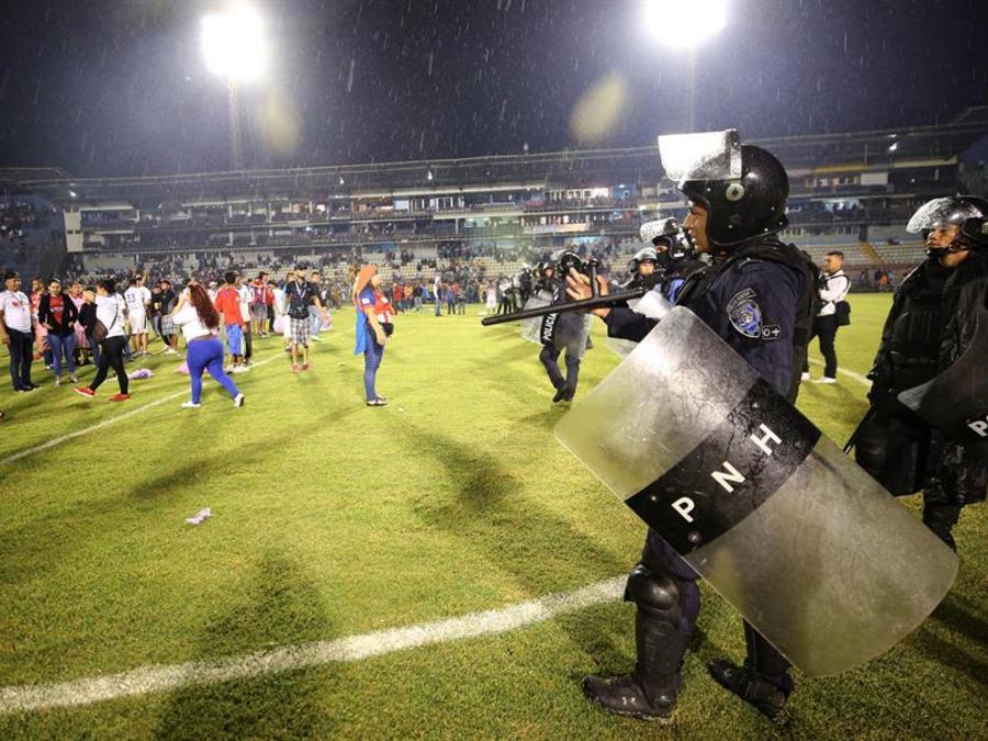 Aficionados ingresan al campo y se protegen de los gases lacrimógenos lanzados por las autoridades, debido a los disturbios a las afueras del Estadio Nacional por la cancelación del clásico entre Olimpia y Motagua hoy sábado, en Tegucigalpa.
