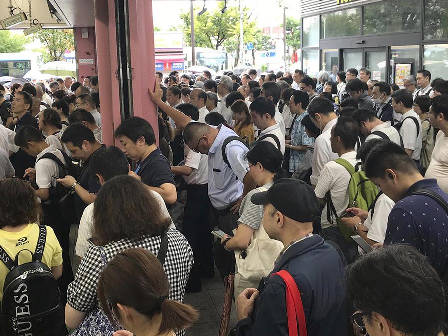 Cientos de japoneses esperan en las afueras del metro en Yokohama, cerca de Tokio, después de que los servicios fueran suspendidoa tras el paso de un tifón.
