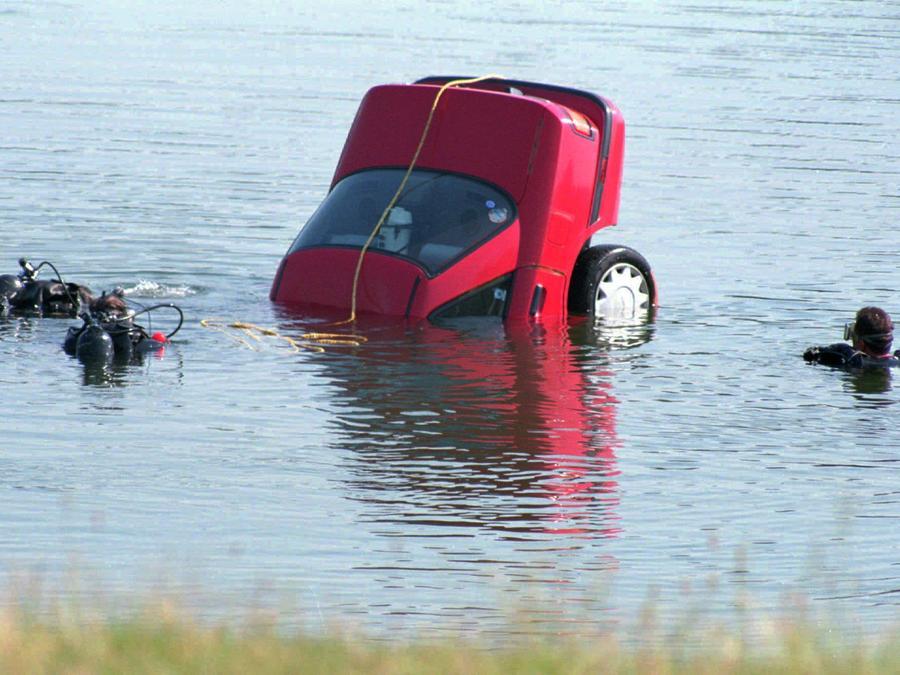Fotogragía de archivo de un equipo de buzos sacando un auto de un lago