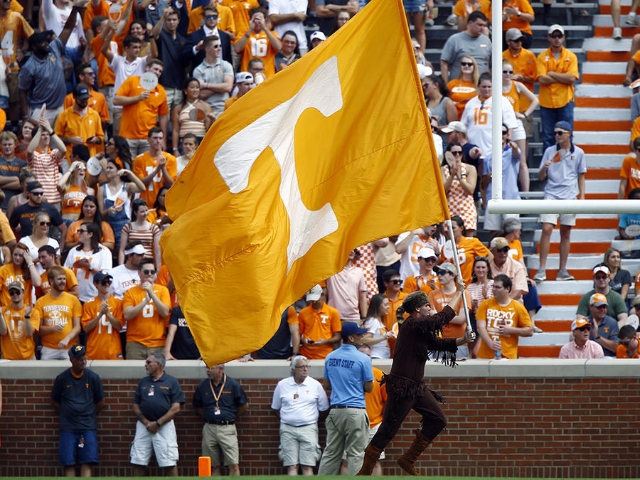 La bandera de la Universidad de Tenneessee ondea en el campo de un juego de fútbol americano.