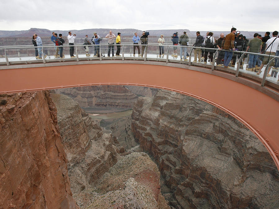 Varias personas caminan en el puente de cristal Skywalk, en el Parque Nacional Gran Cañón.