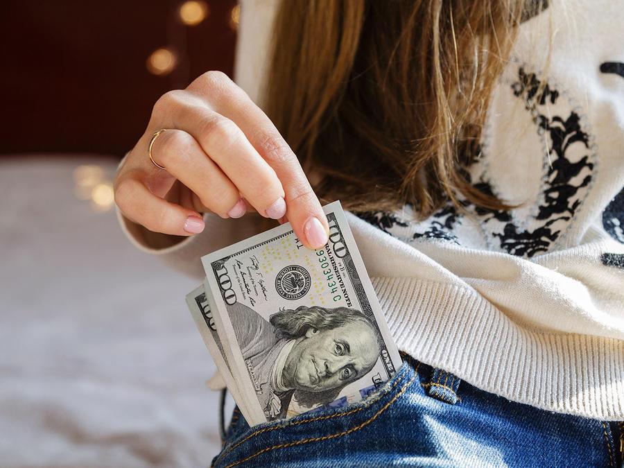 Mujer con billete en el bolsillo