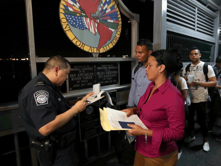 Un oficial de Aduanas revisa los documentos de los inmigrantes que buscan solicitar asilo en Estados Unidos.