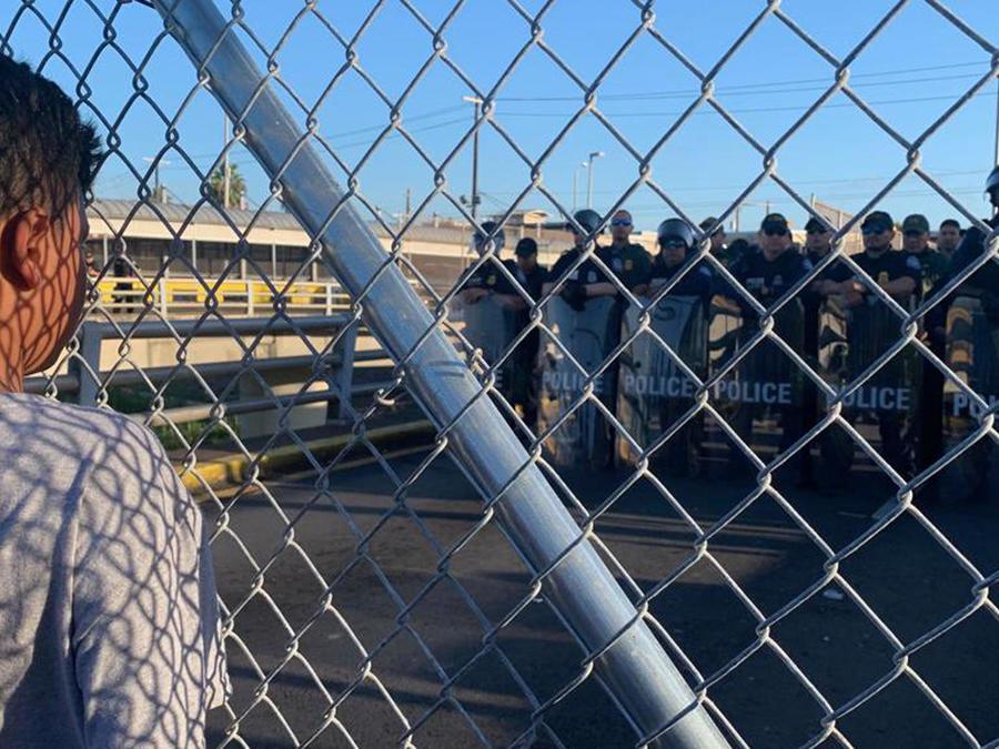 Un niño observa este jueves a agentes de la Patrulla Fronteriza durante una protesta organizada por migrantes en la frontera entre Matamoros México y Brownsville (Texas).