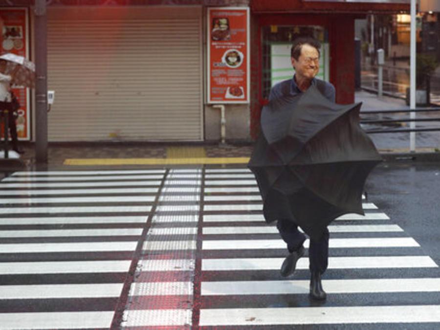 Un hombre cruza estee sábado una calle de Tokio bajo los efectos de un devstardor tifón.