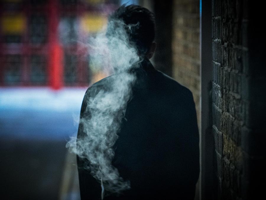 La silueta de un hombe se observa en medio del humo de un cigarro.