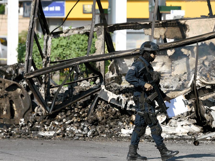 Un policía camino frente a un vehículo incendiado por hombres armados en Culiacán, Sinaloa