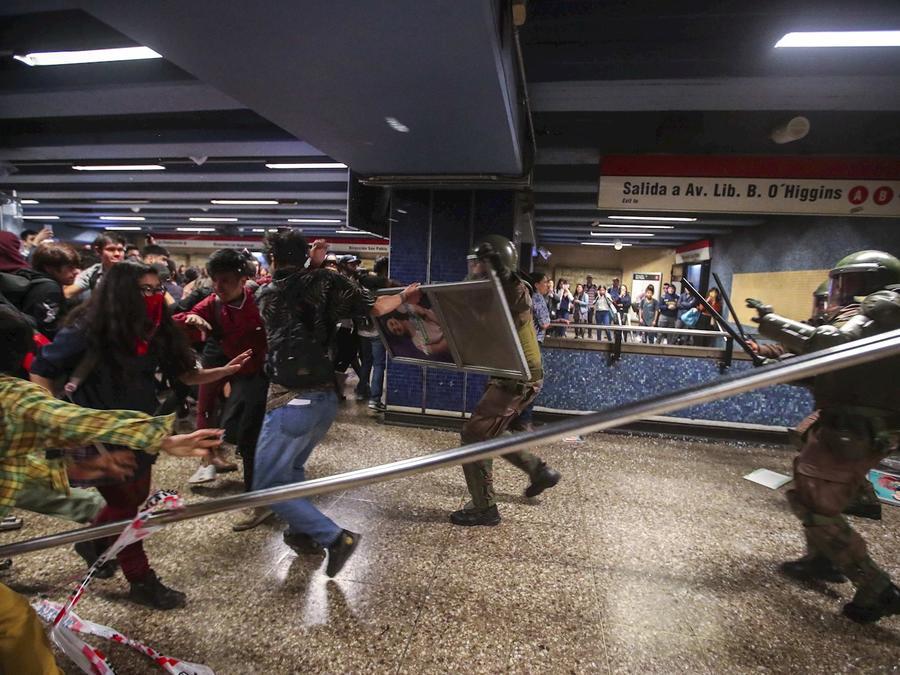 Manifestantes y fuerzas de seguridad se enfrentan este viernes en una de las estaciones del metro de Santiago de Chile.