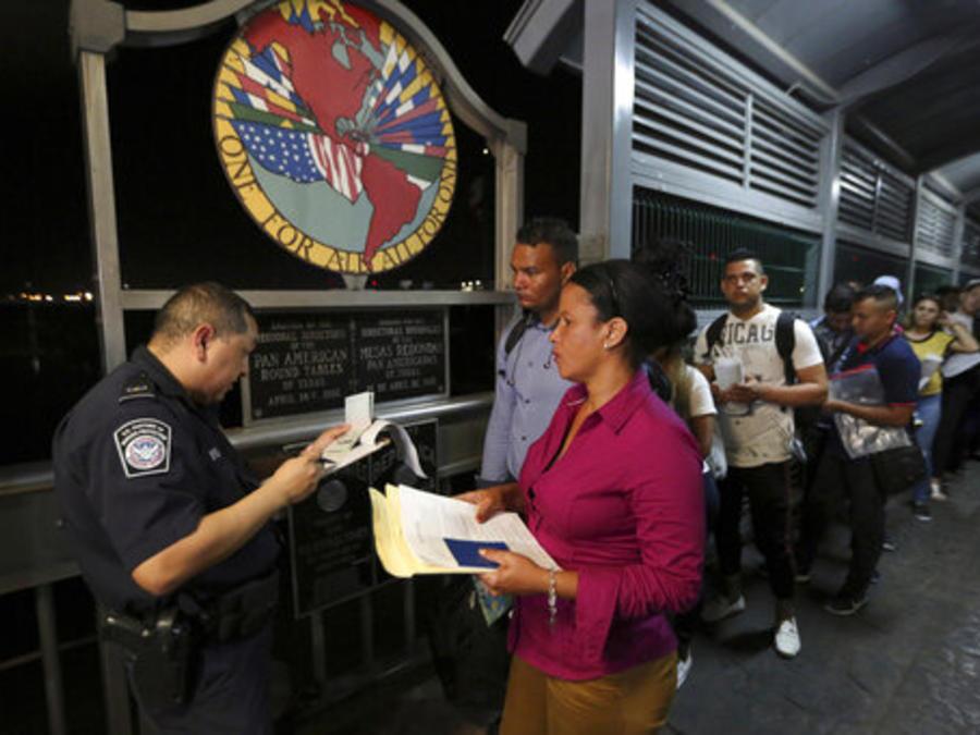 Un funcionario de la Patrulla Fronteriza estadounidense chequea los documentos de algunos migrantes que se dirigen a presentar sus solicitudes de asilo en la frontera de Texas (imagen de archivo).